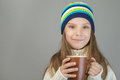 Little girl in knitted cap drinking tea beautiful smiling on gray background Stock Images