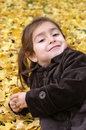 Little girl laying back over yellow leaves Stock Images