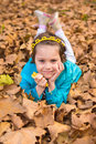 Little girl laying with face on hands in park Royalty Free Stock Photo
