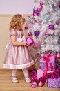 Little girl lays out the gifts under Christmas tree. Royalty Free Stock Photo