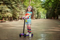 Little girl learn to ride scooter in a park on sunny summer day. Royalty Free Stock Photo