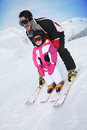 Little girl learning to ski with her father daddy skiing down slope Royalty Free Stock Images