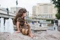 Little girl in a leopard dress sitting on a rock smiling next to fountain Royalty Free Stock Image