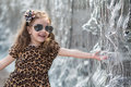 Little girl in a leopard dress touching hand fountain smiling Stock Photo