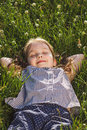 The little girl lies on the grass and dreams. Summer Royalty Free Stock Photo