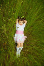 Little girl lies in green grass Stock Photo