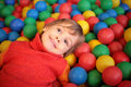 Little girl lies on multi-coloured spheres Royalty Free Stock Photos
