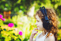 Little girl listening to music on headphones in a summer park Royalty Free Stock Image