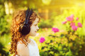 Little girl listening to music on headphones in a summer park i Stock Photo