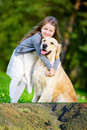 Little girl little girl embraces golden retriever in the park her dog summer Stock Image