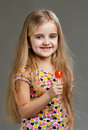 Little girl with lollipop on a grey background Stock Photography