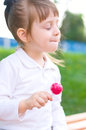 Little girl with lollipop happy outdoors Stock Photo