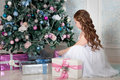 Little girl with long curled hair sitting near christmas tree and gifts christmas time portrait of gift box Royalty Free Stock Photos