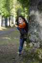 Little girl looking from behind a tree in the woods Royalty Free Stock Photography