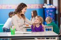 Little girl looking at kindergarten teacher with students in background Stock Photo