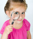 Little girl looking through a magnifying glass Royalty Free Stock Images