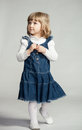 Little girl looking up in blue dress on dark background Royalty Free Stock Photography