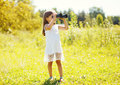 Little girl looks in binoculars outdoors in summer