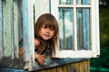 Little girl looks out the window rural house Royalty Free Stock Photo
