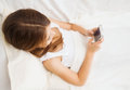 Little girl lying in bed with smartphone at home child technology and internet concept Stock Photography