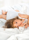 Little girl lying in bed and sucks a finger Royalty Free Stock Photo