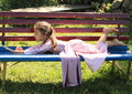 Little girl lying on bench barefoot in lila dress red and blue and having rest Royalty Free Stock Photo