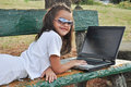Little girl lying on a bench with your computer Royalty Free Stock Photo