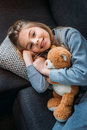 Little girl lying on couch with teddy bear and smiling at camera Royalty Free Stock Photo