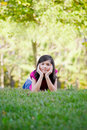 Little girl lying down on grass ten year old chin in hand Stock Images