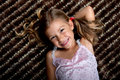 Little girl lying down on a rug and smiling Royalty Free Stock Photo
