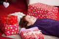 Little girl lying dreaming of christmas day on her back on the living room carpet surrounded by colourful red giftwrapped boxes Stock Photos