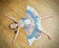 Little girl lying on the floor with legs and hands apart Royalty Free Stock Photo