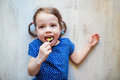 Little girl lying on the floor smiling eating lollipop cute with two braids spaghetti Stock Photos