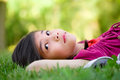 Little girl lying on grass lawn thinking Royalty Free Stock Photography