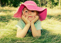 Little girl lying on grass outdoor. Smiling girl face closeup. Royalty Free Stock Photo