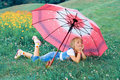 Little girl lying on the grass under the umbrella Royalty Free Stock Photography
