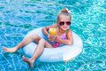 Little girl lying on inflatable ring in swimming pool. In the hands of a glass of mango juice. Holidays. Royalty Free Stock Photo