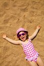 Little girl lying on sandy beach Royalty Free Stock Image