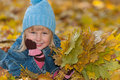 Little girl is lying on the yellow leaves a in autumn Royalty Free Stock Photo