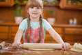 Little girl makes dough on kitchen with rolling pin Royalty Free Stock Photo