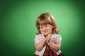 Little girl making faces portrait of a against green background Royalty Free Stock Photo