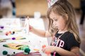 Little girl making handcraft at a table kids party Stock Photos
