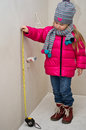 Little girl with measure tape a in winter clothes at newly built home pretending to the wall Royalty Free Stock Photography