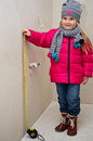 Little girl with measure tape a in winter clothes at newly built home pretending to the wall Stock Images