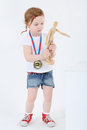 Little girl with medal on chest stands and holds wooden dummy white background Royalty Free Stock Images
