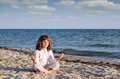 Little girl meditating on the beach Royalty Free Stock Image