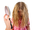 Little girl with messy tangled hair on white a has tangles and a brush is being held up a isolated background for a dresser or Royalty Free Stock Photo