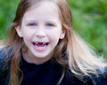 Little girl missing two front teeth outside smiling childhood milestone Stock Images
