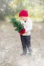Little Girl In Mittens Holding Small Christmas Tree with Snow Effe Royalty Free Stock Photo