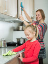 Little girl and mom tidy up at kitchen Royalty Free Stock Photo